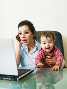 Flexible Working Parent, using a phone & laptop while holding a child